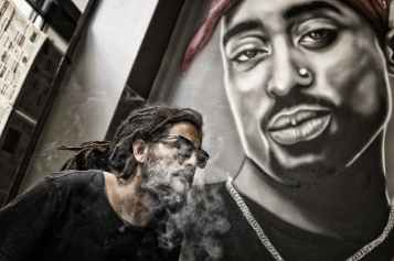 man with dreadlocks and sunglasses poses near tupac shakur portrait